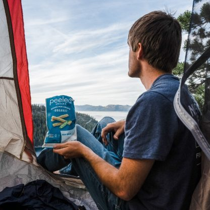 man camping with sea salt pea crisps